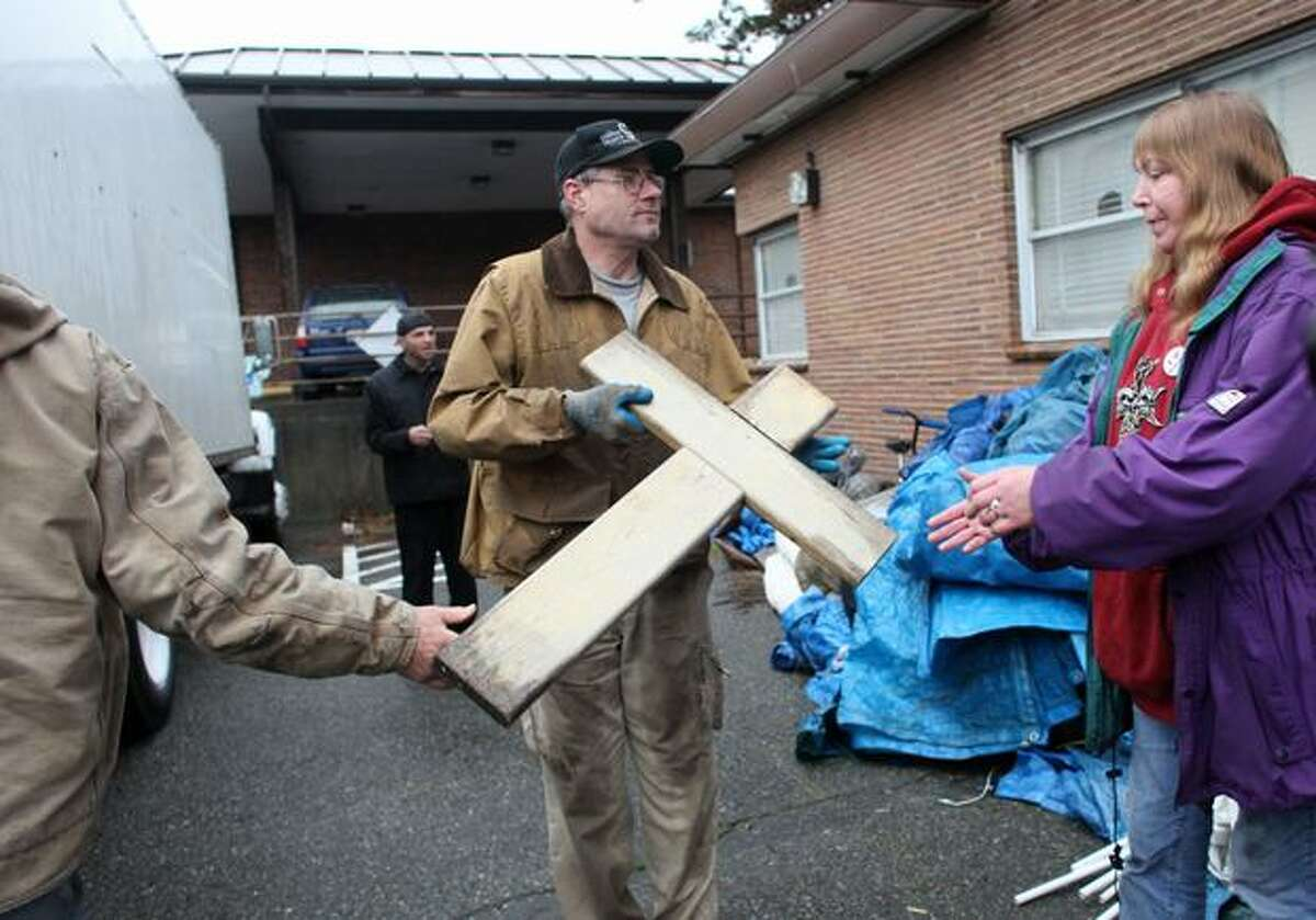 Rodger Mathis passes a cross to Kim Kowalski as they unload personal items as