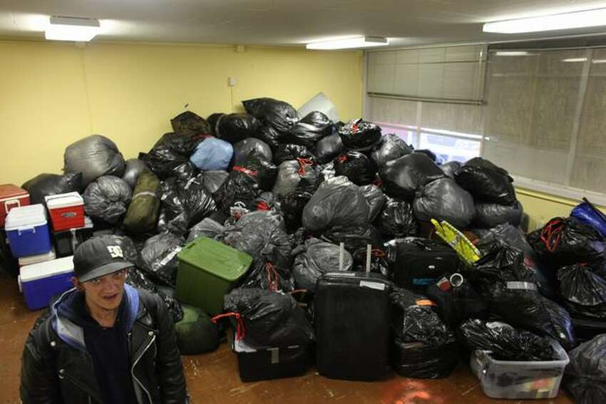 Resident Justin Glines helps stack personal belongings onto a pile as
