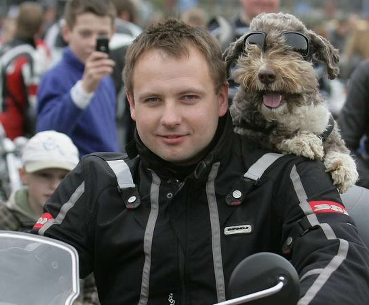 A biker poses with his dog as thousand participants take part in the opening day of the bikers season, in Vilnius.