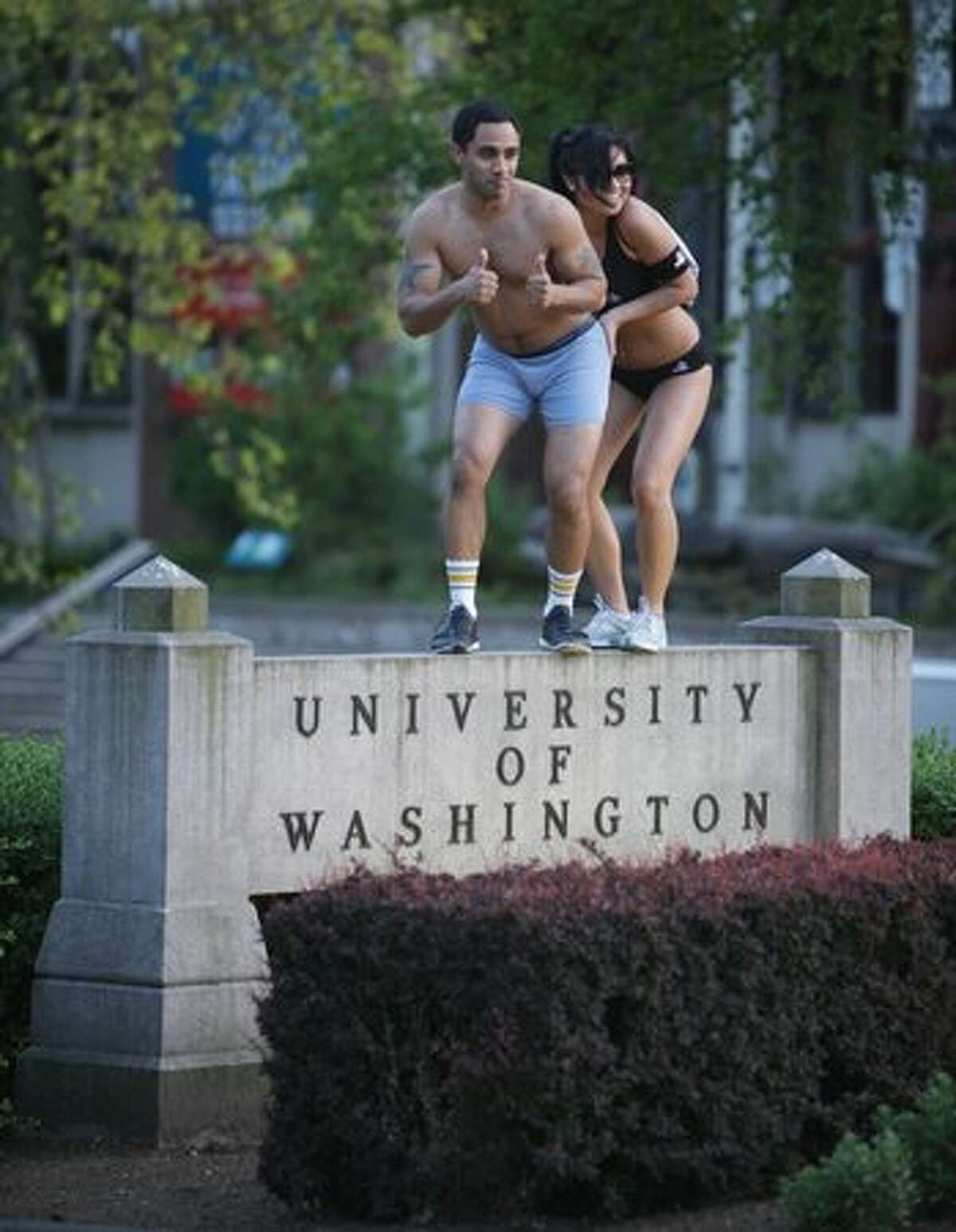 A pair of University of Washington students strike a pose at the entrance to campus during the