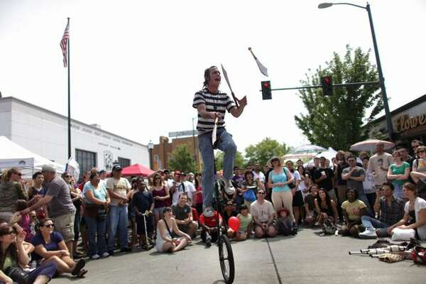 Street Show Keith Wolf juggles blades while riding a unicycle during the annual University District Street Fair on Saturday May 15, 2010 along University Way in Seattle. The festival kicks off the local festival scene with two days of food, music, dancing and blocks of street vendors.