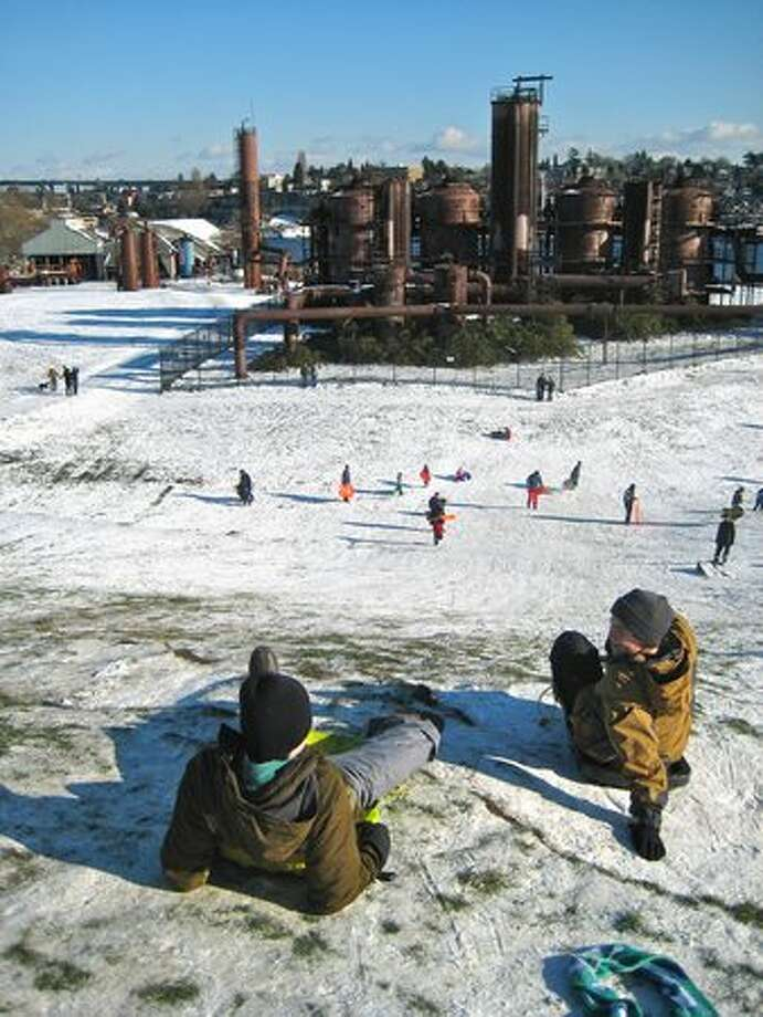 Kids of all ages slip and slide down Kite Hill at Gasworks Park on Tuesday afternoon. Photo: David Horsey, Seattlepi.com