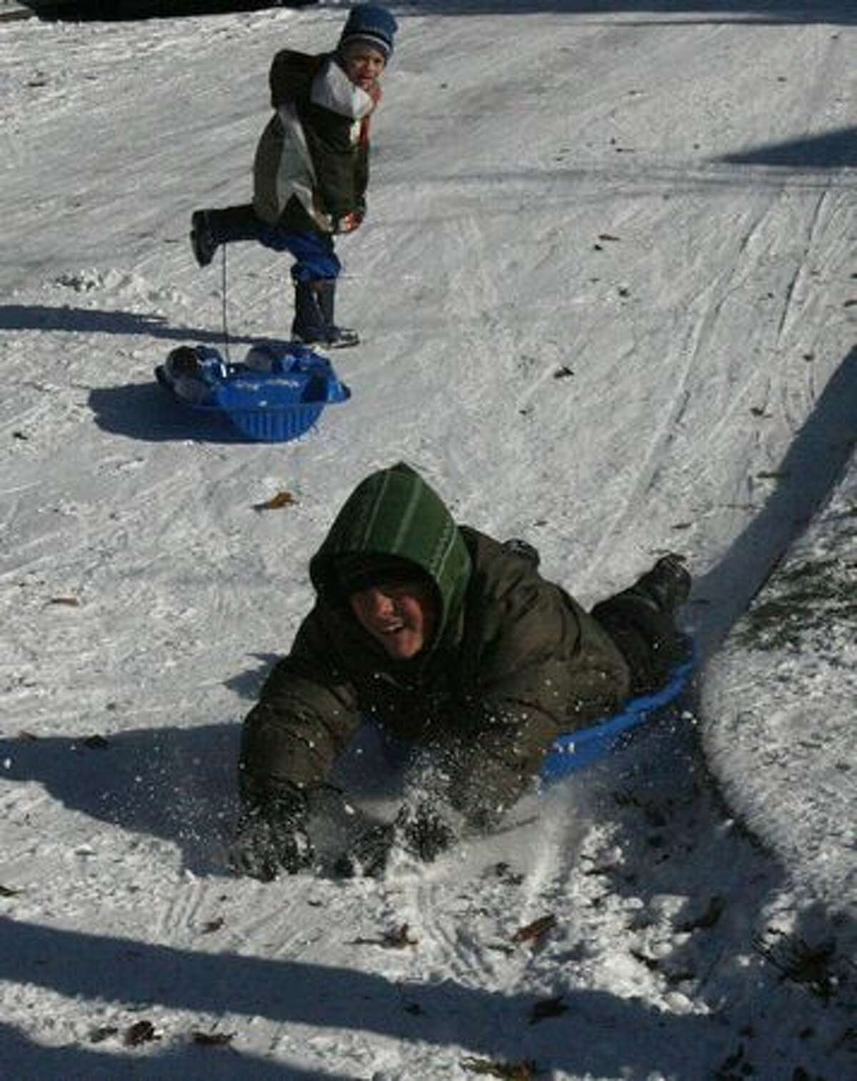 Truman Wisen, 8, finishes a sled run as brother Hamilton Wisen, 4, watches in Seattle's Ballard neighborhood on Tuesday.