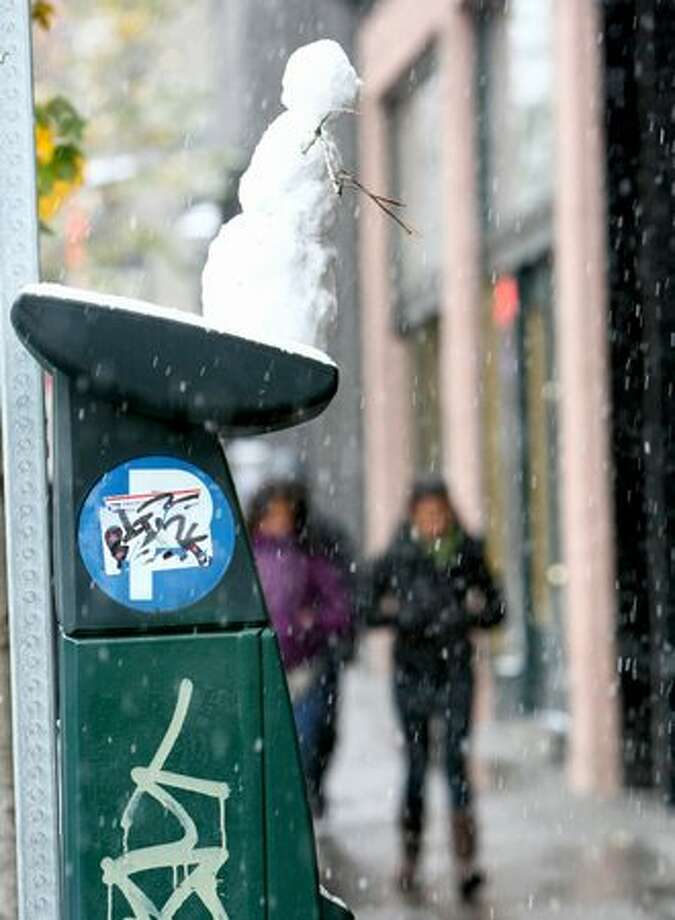 A snowman is perched atop a parking pay station during the first snowfall of the season at East Pike Street in Seattle's Capitol Hill neighborhood. Photo: Joshua Trujillo, Seattlepi.com