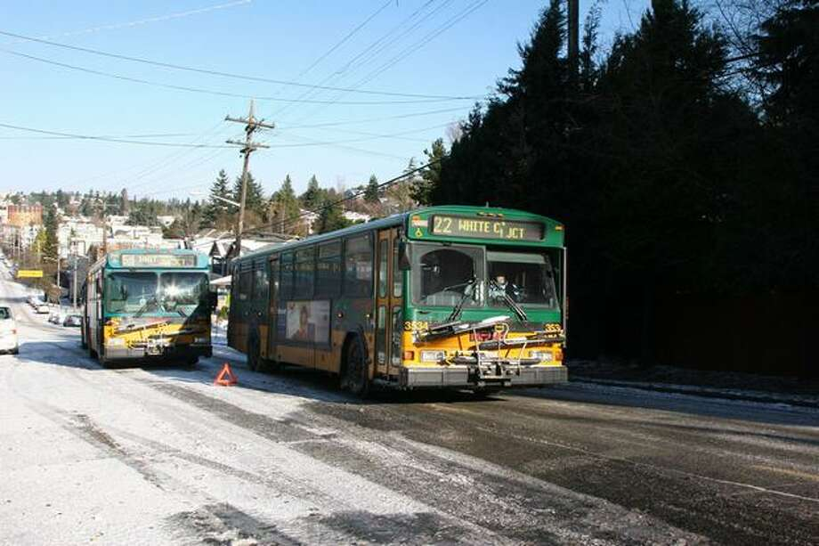A bus on Metro's Route 22 passes another bus stuck on California Avenue Southwest near Southwest Othello Street in West Seattle Tuesday afternoon. As many as 200 Metro buses were stranded at times during Monday's snowstorm. The transit agency said tow trucks should be able to reach stuck buses more quickly on Tuesday because of lighter traffic and improved road conditions. Photo: Michelle Nicolosi, Seattlepi.com