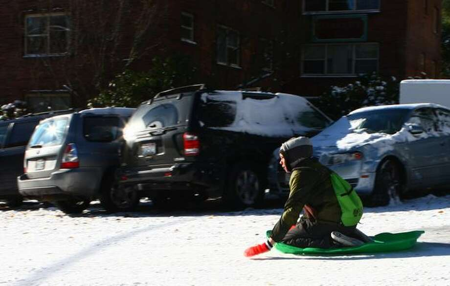 Peter Walhout, 13, makes good use of the ice and snow Tuesday on Queen Anne Avenue North as he barrels by a line of cars smashed the previous night. Photo: Levi Pulkkinen, Seattlepi.com