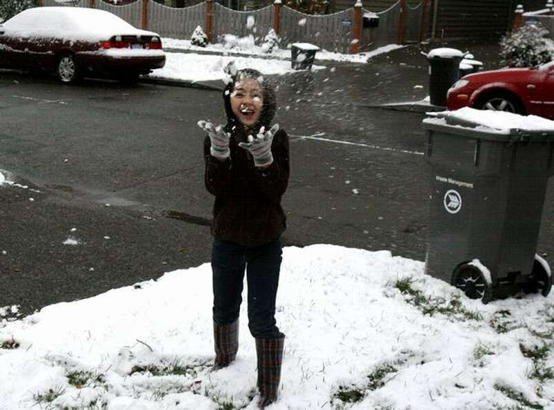 Teresa Reyes, 10, tosses snow in the air in Seattle's Ballard neighborhood on Monday.