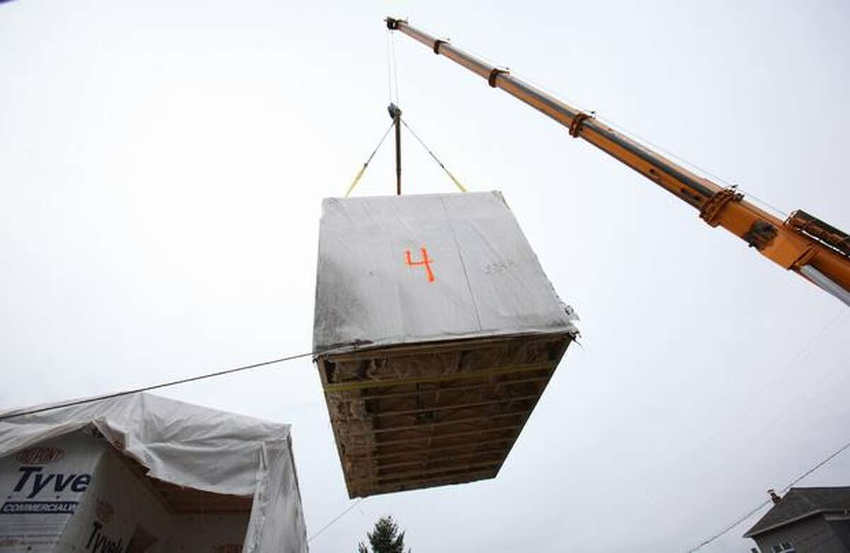 A crane positions a second-floor section of the Greenfab modular home.