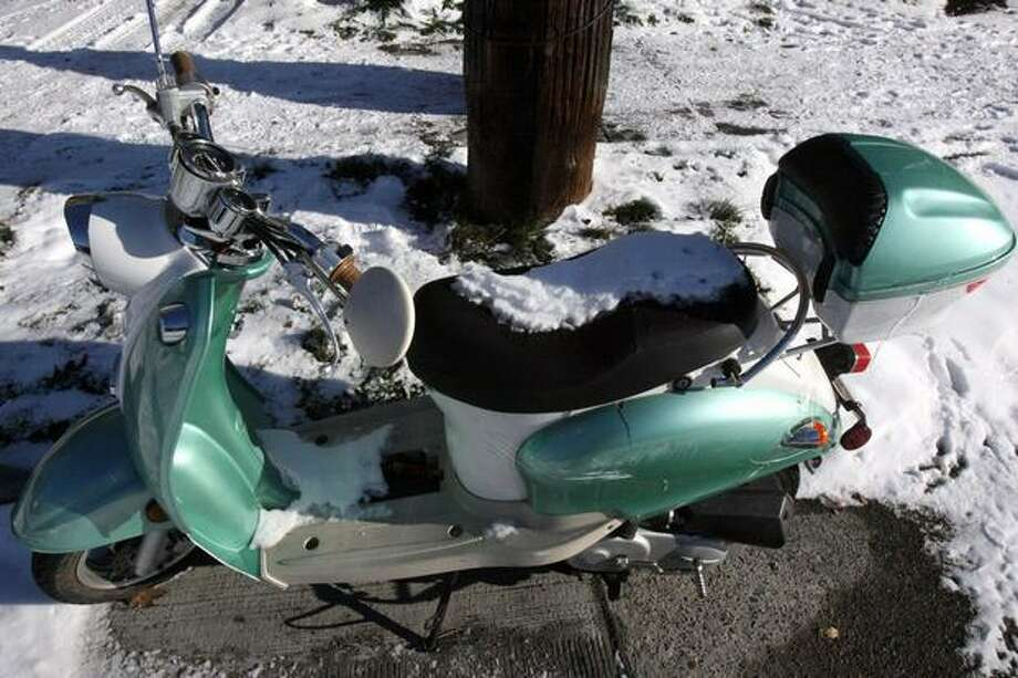 A snow-covered scooter sits on a street in Seattle's Ballard neighborhood on Tuesday. Photo: Aubrey Cohen, Seattlepi.com