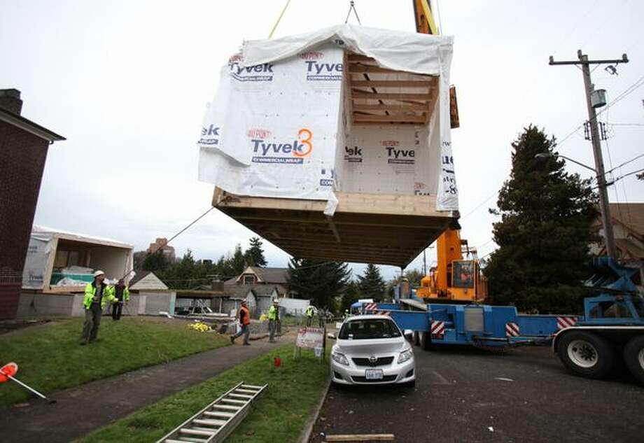 a crane positions a section of a modular home on south lane