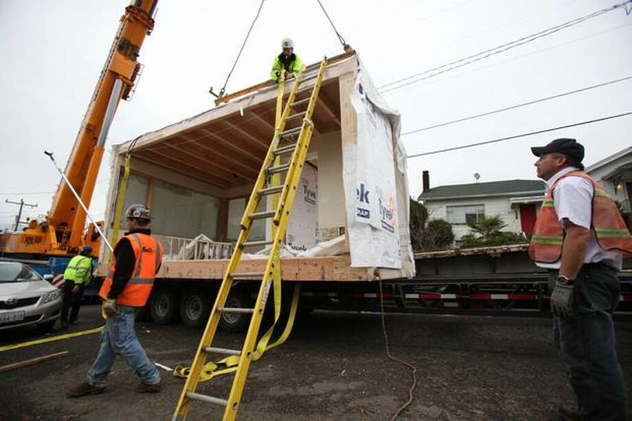 Crews unwrap a section of a Greenfab modular home on South Lane Street in Seattle's Jackson Place neighborhood on Tuesday, December 7, 2010. The home is being touted as a first of its kind green modular home in the city. Photo: Joshua Trujillo, Seattlepi.com