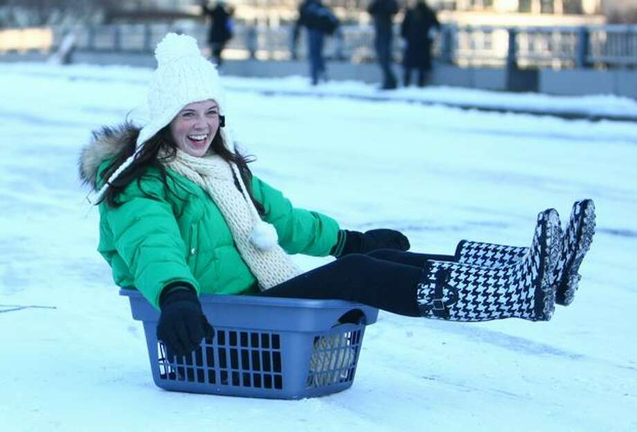 Tessa Archer speeds down East Denny Way in her laundry basket after snow and ice wreaked havoc with Seattle-area roads. Earlier in the morning, a group of sledders were injured on Denny Way when a car turned up the street, colliding with the sledders. Photographed on Tuesday, Nov. 23, 2010. Photo: Joshua Trujillo, Seattlepi.com