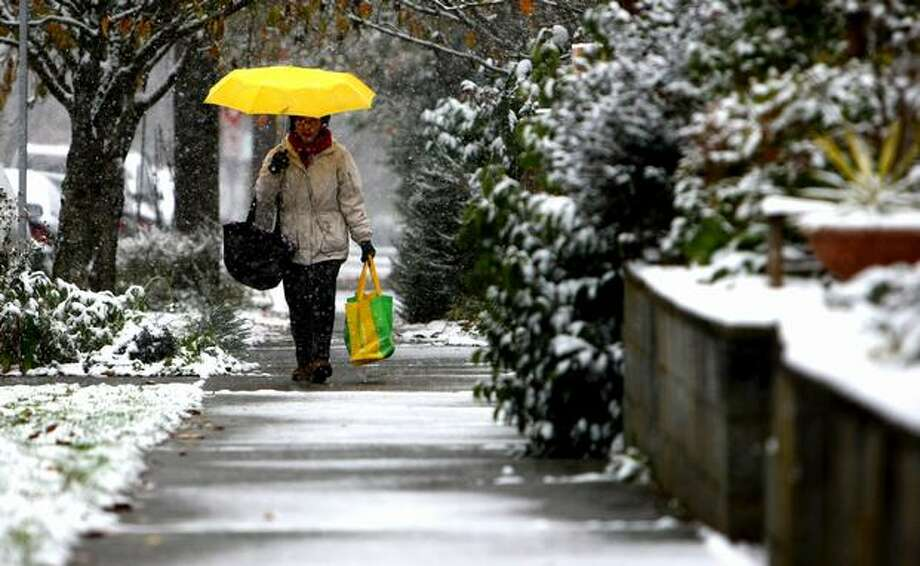 A woman walks through Seattle's Capitol Hill neighborhood during the first snowfall of the season on Monday. Photo: Joshua Trujillo, Seattlepi.com