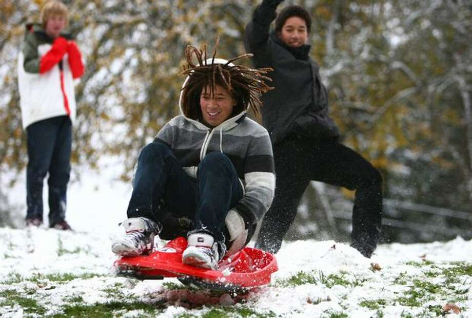 Nathan Hale High School student Alex Meacham sleds down a hill after an early release from school because of snow on Monday at Meadow Brook Park in north Seattle. Seattle Schools released students early because of the weather. Photo: Joshua Trujillo, Seattlepi.com