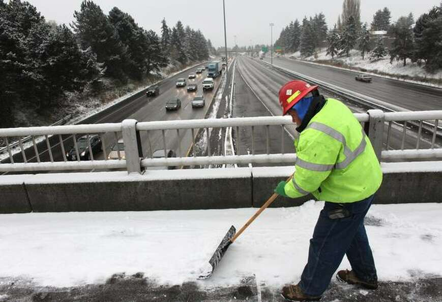 Seattle Department of Transportation employee Marcus Leorna shovels snow on the North 92nd Street ov