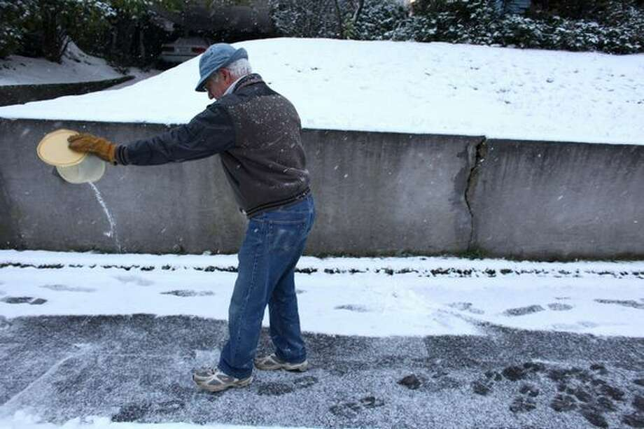 Dan Brannen sprinkles ice cream salt on the sidewalk in front of his Beacon Hill home. Photo: Joshua Trujillo, Seattlepi.com