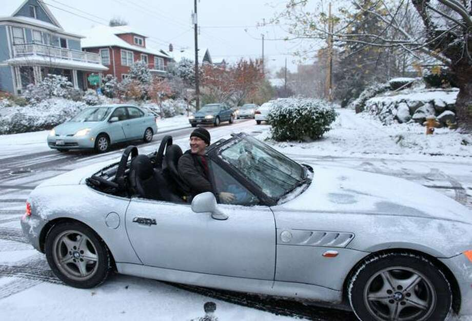 "Sam Good pulls his convertible car into traffic during the first snowfall of the season in Seattle. ""This is gorgeous,"" he said of the falling snow. ""I get to be snowed on while driving. If I was at home I'd be out in it too,"" he said. Photo: Joshua Trujillo, Seattlepi.com"