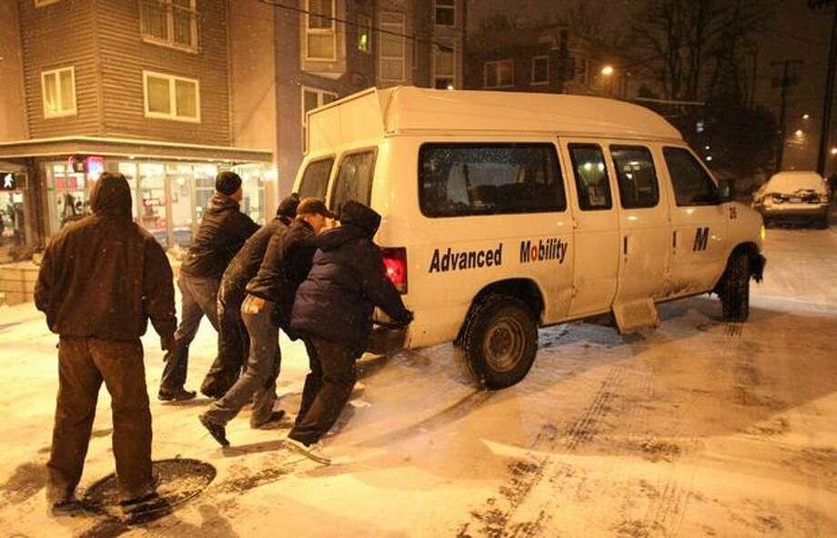 People push a van on Bellevue Avenue in Seattle's Capitol Hill neighborhood. Photo: Joshua Trujillo, Seattlepi.com