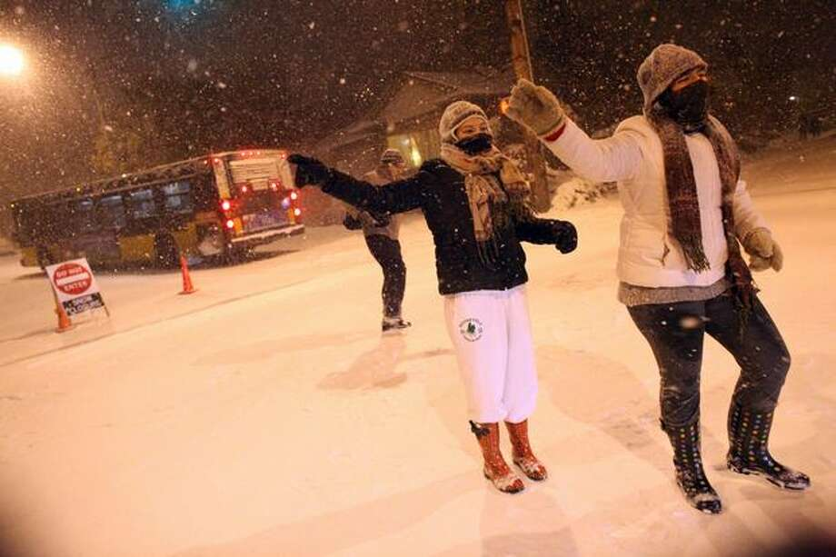 Myriah Juarez Wagner and Jessica Juarez direct traffic away from a slick street on 12th Avenue NE in Seattle's Roosevelt neighborhood on Monday, November 22, 2010. (Joshua Trujillo, Seattlepi.com)...