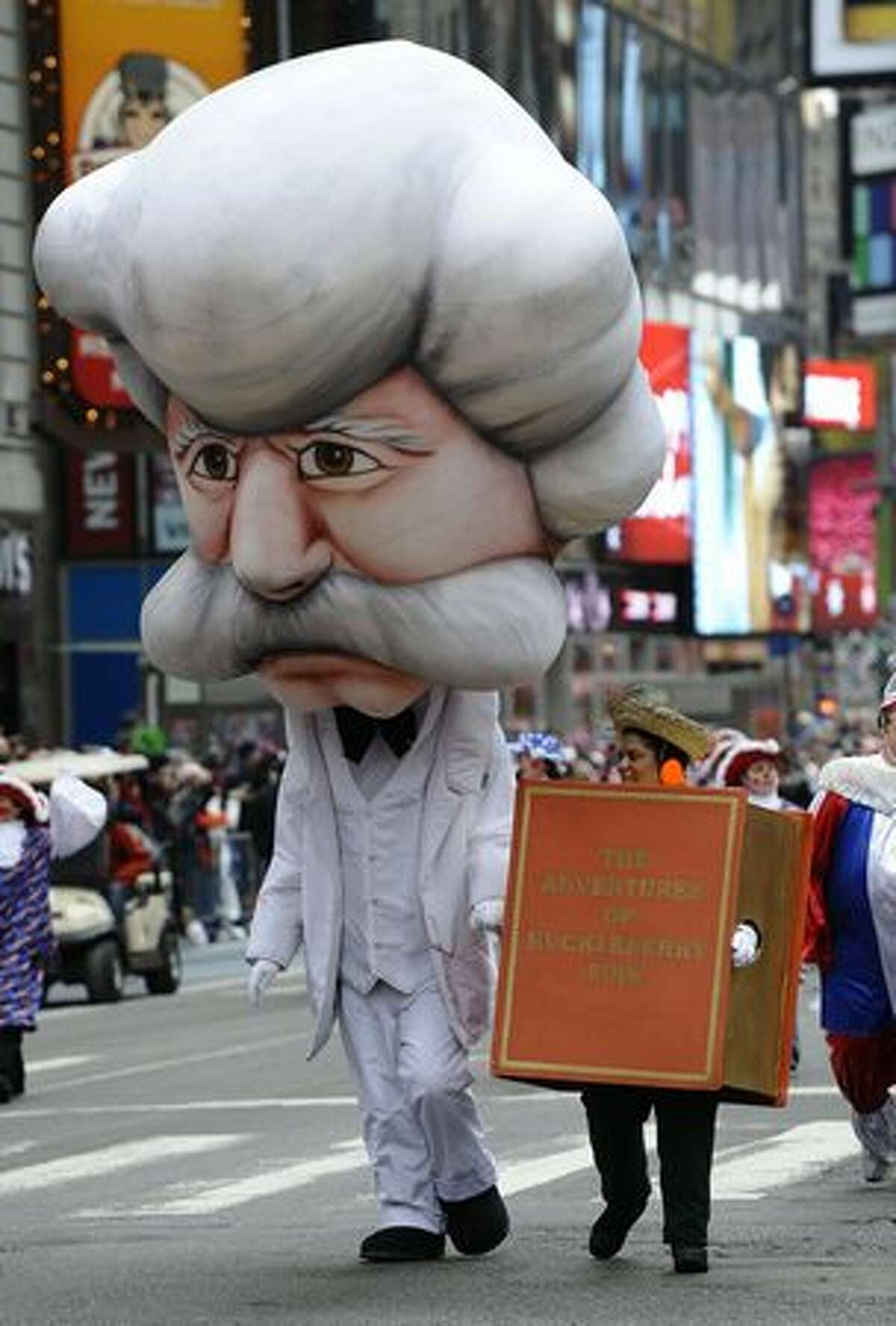 A person dressed as author Mark Twain comes down 7th Ave in Times Square joining the giant balloon lineup for the 84th annual Macy's Thanksgiving Day Parade in New York. AFP PHOTO / (TIMOTHY A. CLARY/AFP/Getty Images)