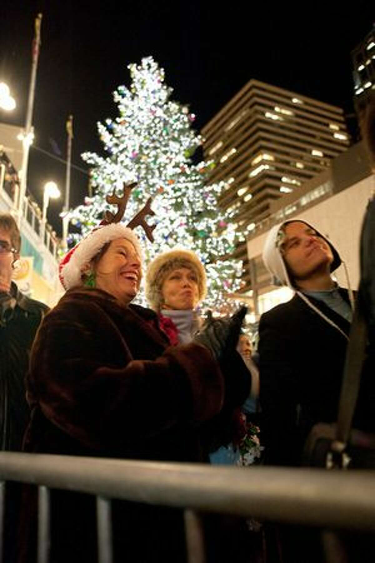 Donna Brown, left, and Wister Kay, center, share a laugh as carolers perform on stage.
