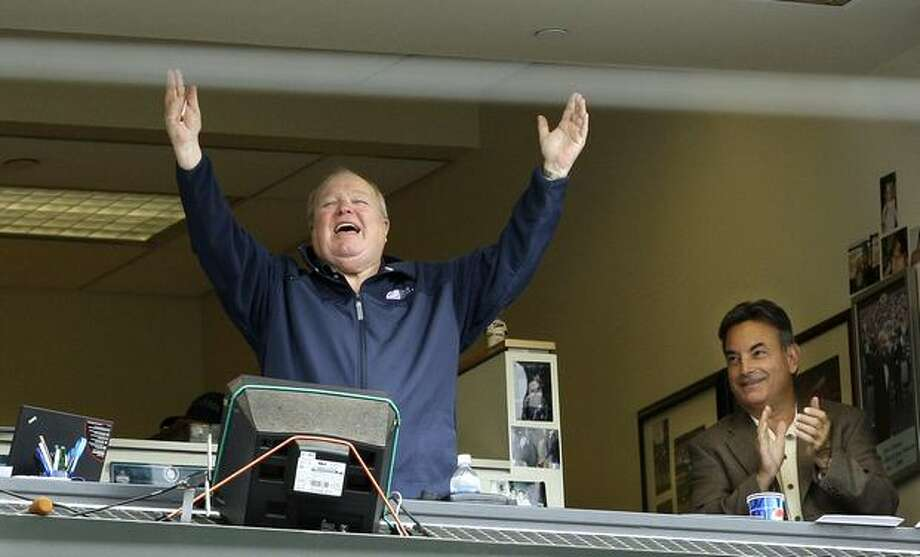 Broadcaster Dave Niehaus raises his arms from the booth as he is introduced to the crowd during a July 23, 2008 baseball game between the Mariners and Boston Red Sox. Fellow broadcaster Rick Rizzs is at right. (Elaine Thompson/The Associated Press/seattlepi.com file) Photo: P-I File
