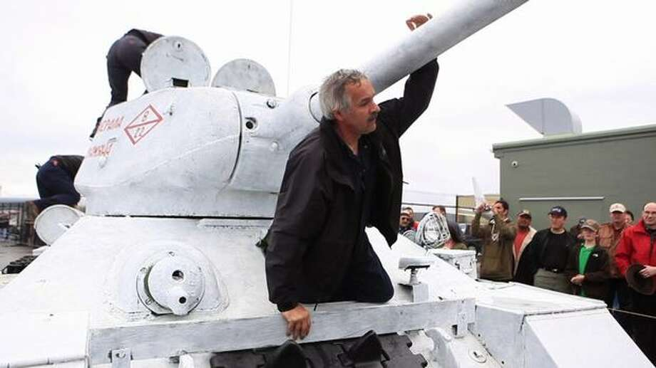 Mark Kepler climbs out of a Soviet T-34 tank after driving it. Photo: Joshua Trujillo, Seattlepi.com