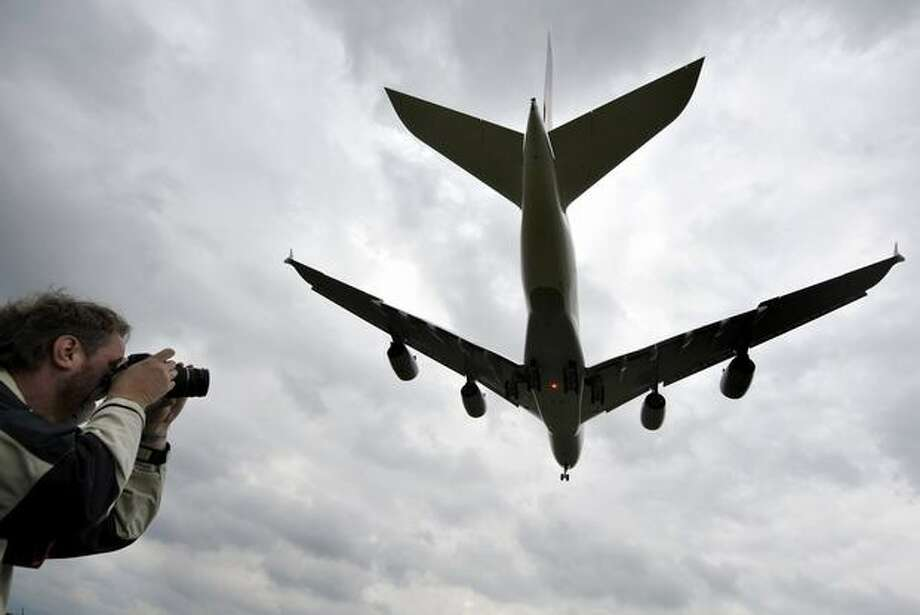 A man takes pictures of an Airbus A380 of German airline Lufthansa flying next to the village of Rheinmuenster, southern Germany, during a landing training for pilots on May 31, 2010 at the airport in Baden-Baden. The German national football team will use this A380 when they travel on June 6, 2010 to South Africa to take part in the 2010 Football World Cup. Photo: Getty Images
