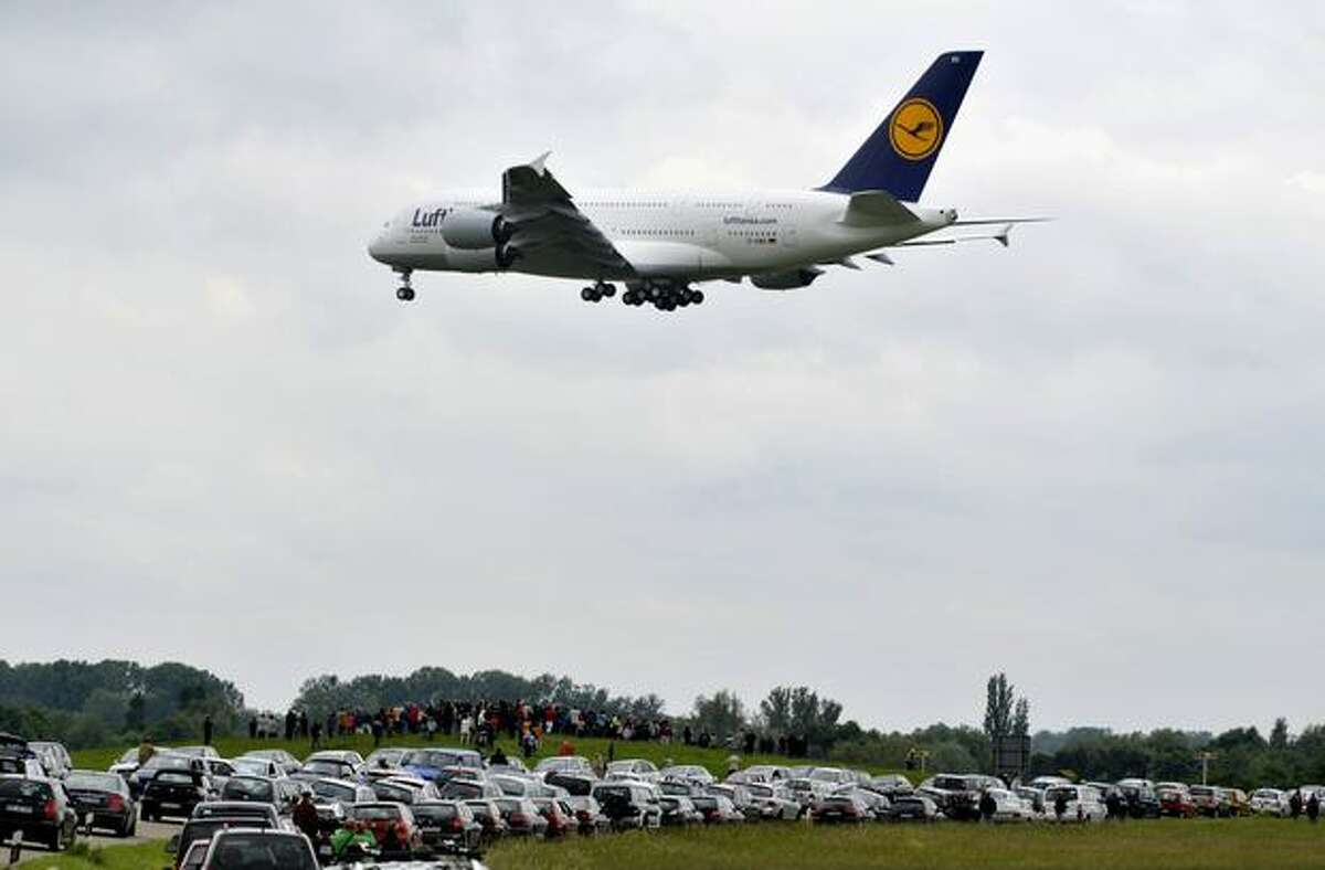 Spectators standing next to the village of Rheinmuenster, southern Germany, look to an Airbus A380 of German airline Lufthansa flying towards the airport of Baden-Baden during a landing training for pilots on May 31, 2010. The German national football team will use this A380 when they travel on June 6, 2010 to South Africa to take part in the 2010 Football World Cup.