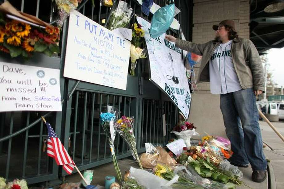 Seattle Mariner fan Brian Bell of Redmond adds to a growing memorial for longtime Mariner broadcaster Dave Niehaus at the gates of Safeco Filed on Thursday, November 11, 2010. Niehaus died of a heart attack on Wednesday. (Joshua Trujillo, Seattlepi.com) Photo: P-I File