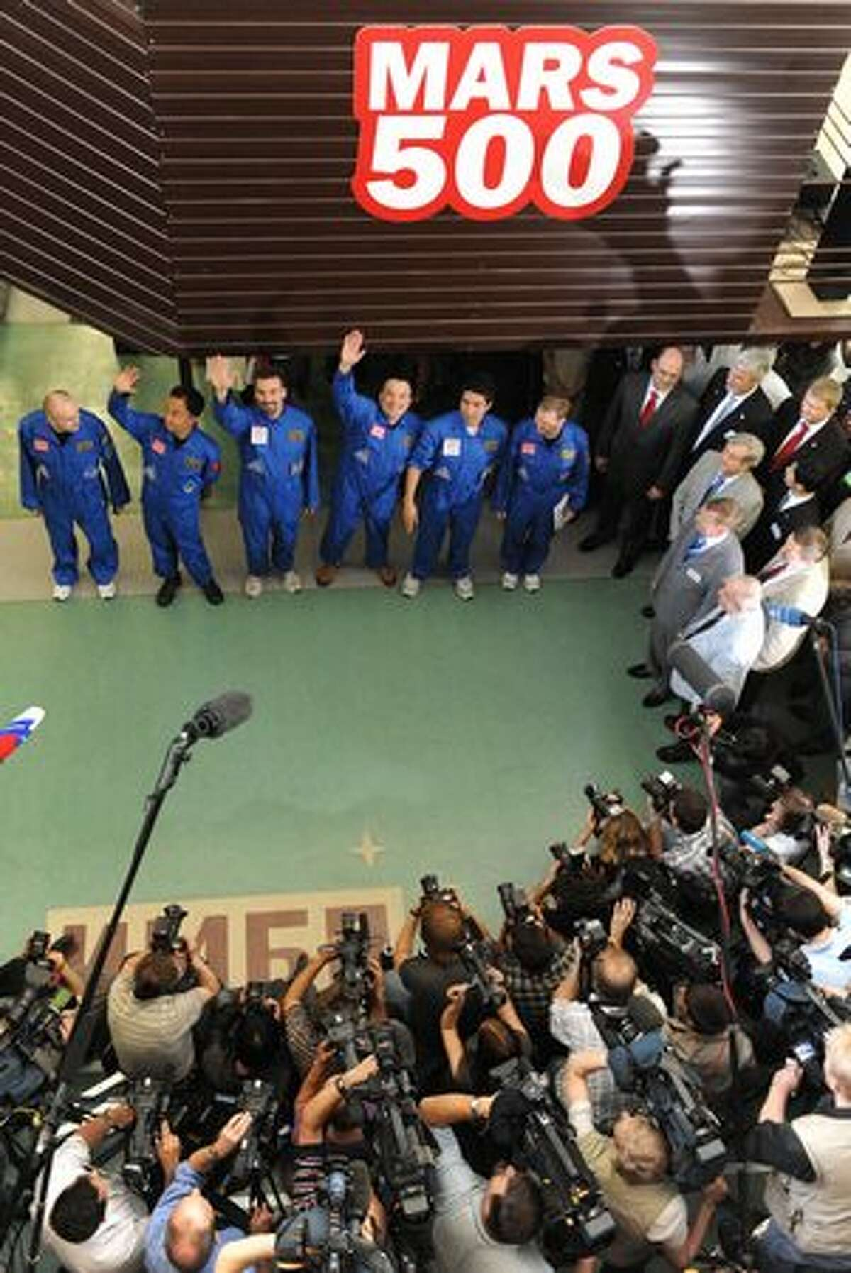 Mars500 crew members (from left) Alexey Sitev, of Russia, Wang Yue, of China, Romain Charles, of France, Sukhrob Kamolov, of Russia, Diego Urbina, of Italy and Alexander Smoleevskiy, of Russia wave before being locked into the Mars500 isolation facility in Moscow.