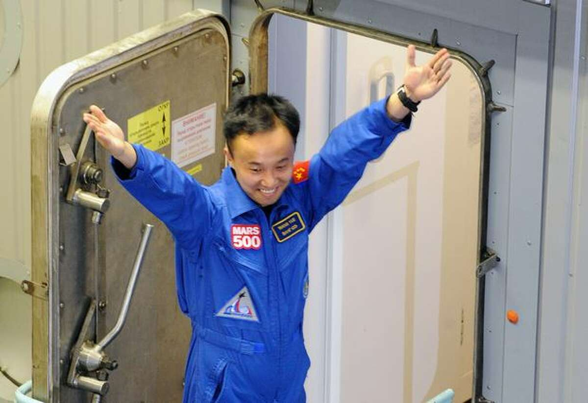 Mars500 crew member Wang Yue, of China, gestures before entering and being locked into the Mars500 isolation facility in Moscow.