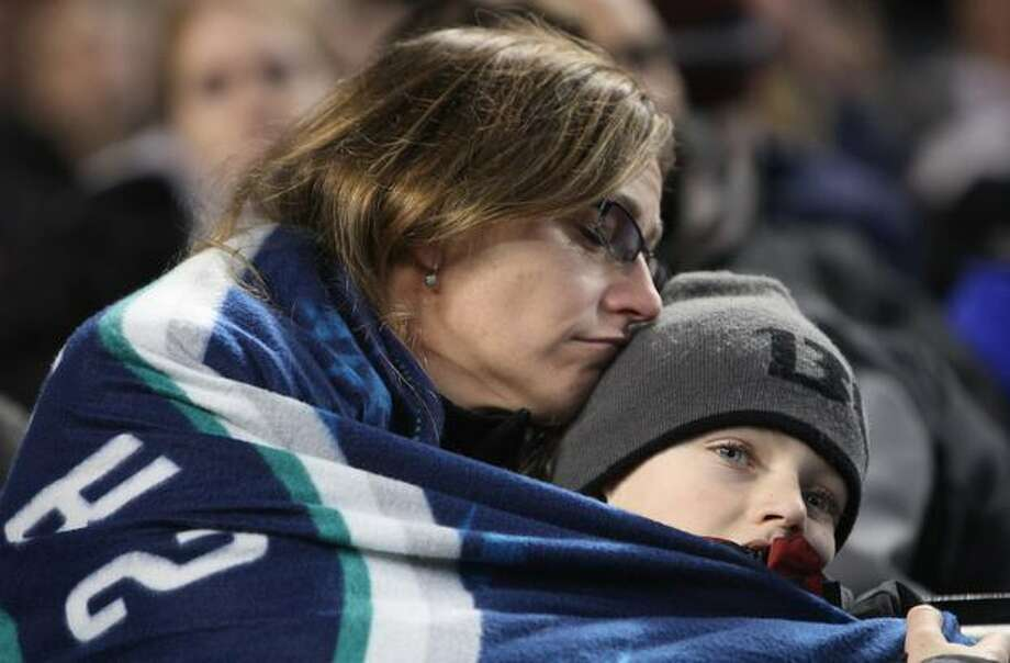 Sherry Locke of Federal Way embraces her son Brandon, 9, during a celebration of life ceremony for Seattle Mariners broadcaster Dave Niehaus on Saturday, December 11, 2010 at Safeco Field. The longtime voice of the Mariners passed away last month. (Joshua Trujillo, Seattlepi.com)... Photo: P-I File