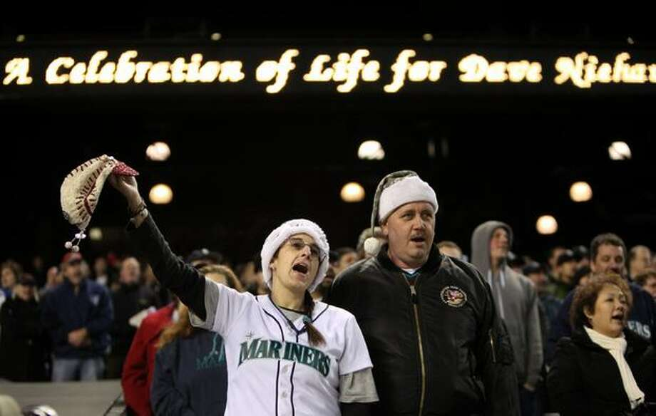 "Amy Franz and Joe Franz of Algona sing ""Take Me Out To The Ball Game"" during a celebration of life ceremony for Seattle Mariners broadcaster Dave Niehaus on Saturday, December 11, 2010 at Safeco Field. The longtime voice of the Mariners passed away last month. (Joshua Trujillo, Seattlepi.com)... Photo: P-I File"