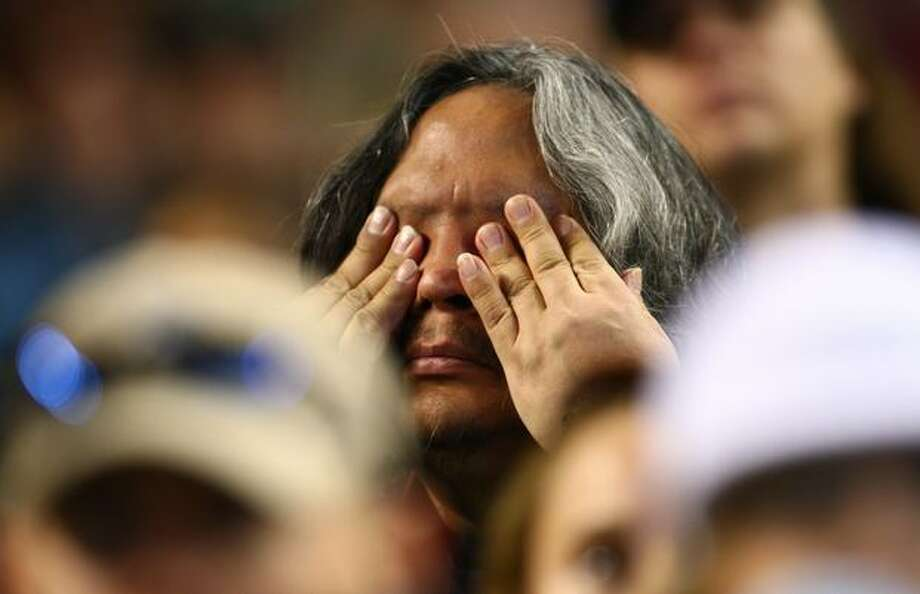 An emotional fan wipes his eyes during a celebration of life ceremony for Seattle Mariners broadcaster Dave Niehaus on Saturday, December 11, 2010 at Safeco Field. The longtime voice of the Mariners passed away last month. (Joshua Trujillo, Seattlepi.com)... Photo: P-I File