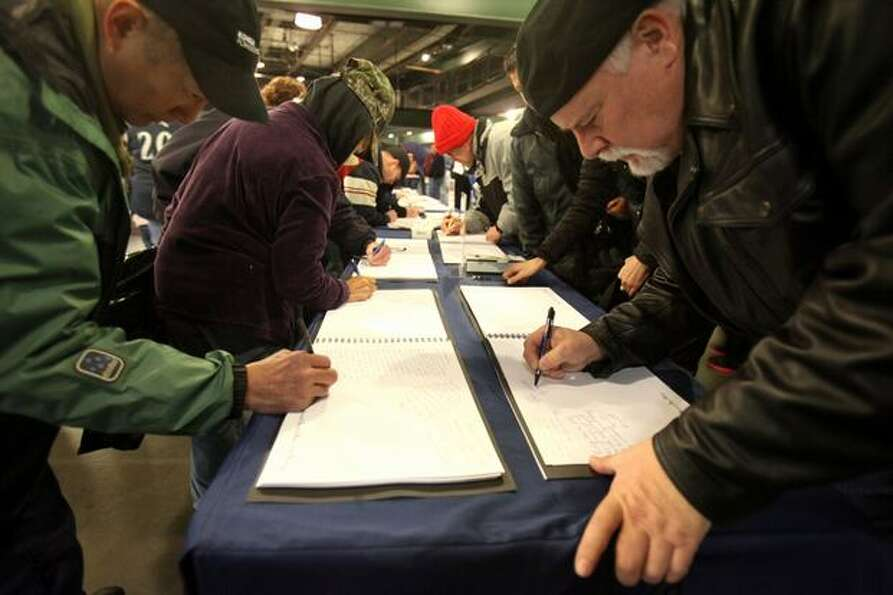 Fans sign memorial books during a celebration of life ceremony for Seattle Mariners broadcaster Dave
