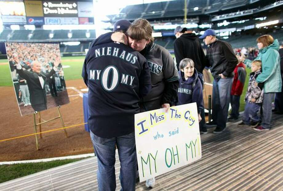 Colleen Doser embraces her boyfriend Noel Renggli during a tribute for Dave Niehaus on Saturday, November 13, 2010 at Safeco Field in Seattle. Niehuas died earlier in the week from a heart attack. The popular play-by-play announcer was the voice of the Seattle Mariners since the team's inaugural season in 1977. (Joshua Trujillo, Seattlepi.com) Photo: P-I File