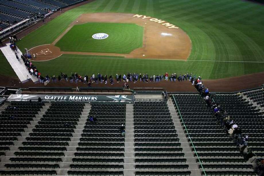 Seattle Mariners fans wait in line to greet the family and friends of Mariners broadcaster Dave Niehaus during a tribute to the voice of the Mariners on Saturday, November 13, 2010 at Safeco Field in Seattle. Niehuas died earlier in the week from a heart attack. The popular play-by-play announcer was the voice of the MBL team since the team's inaugural season in 1977. (Joshua Trujillo, Seattlepi.com) Photo: P-I File