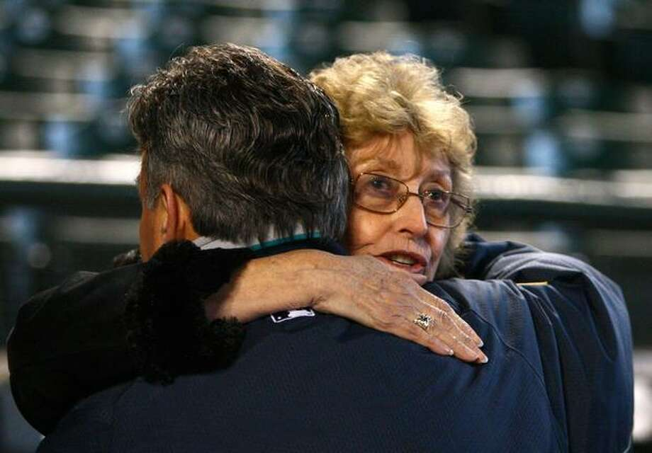 Marilyn Niehaus embraces play-by-play announcer Rick Rizzs during a tribute to Marilyn's late husband Dave Niehuas on Saturday, November 13, 2010 at Safeco Field in Seattle. Niehuas died earlier in the week from a heart attack. Niehaus was the Mariners' play-by-play announcer since the team's inaugural season in 1977. (Joshua Trujillo, Seattlepi.com) Photo: P-I File