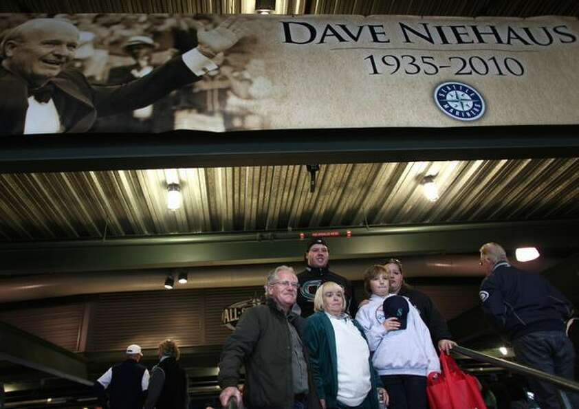 Fans are photographed under a banner of Dave Niehaus during a Nov. 13, 2010 tribute for Niehaus at S