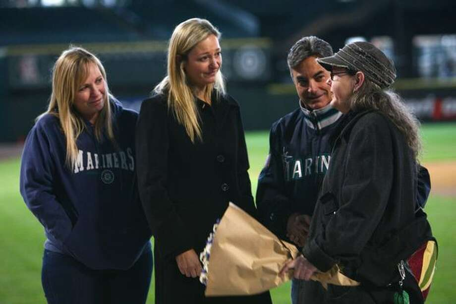 A fan pays her respects to play-by-play announcer Rick Rizzs, second from right, and Dave Niehaus' daughter, Greta Niehaus Dunn, during a Nov. 13, 2010 tribute to the broadcaster. (Joshua Trujillo, Seattlepi.com) Photo: P-I File