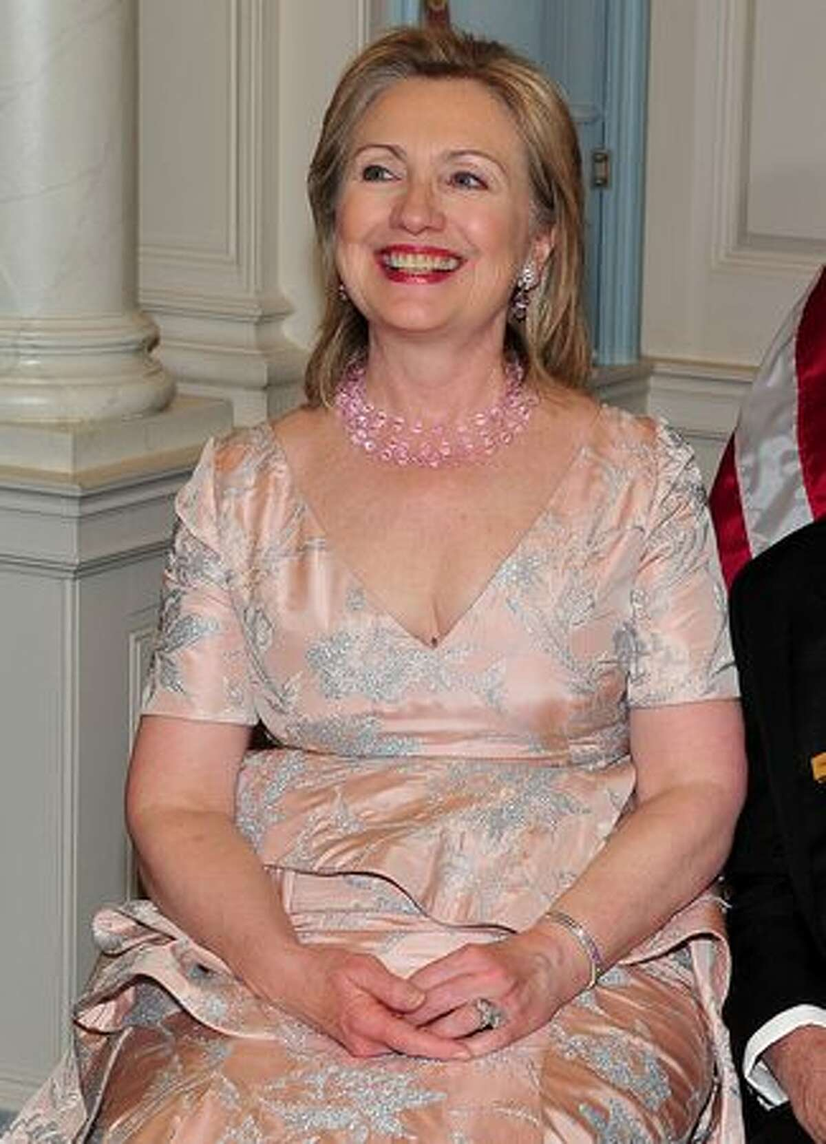 United States Secretary of State Hillary Rodham Clinton smiles as she joins the 2010 Kennedy Center honorees for their formal class photo following the formal Artist's Dinner at the United States Department of State in Washington, D.C. (Photo by Ron Sachs-Pool/Getty Images).