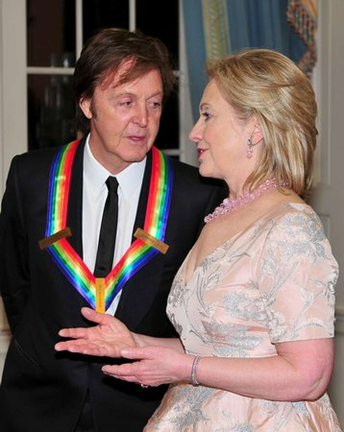 Sir Paul McCartney, one of the 2010 Kennedy Center honorees, shares some thoughts with United States Secretary of State Hillary Rodham Clinton as they prepare to pose for their formal class photo following the formal Artist's Dinner at the United States Department of State in Washington, D.C.