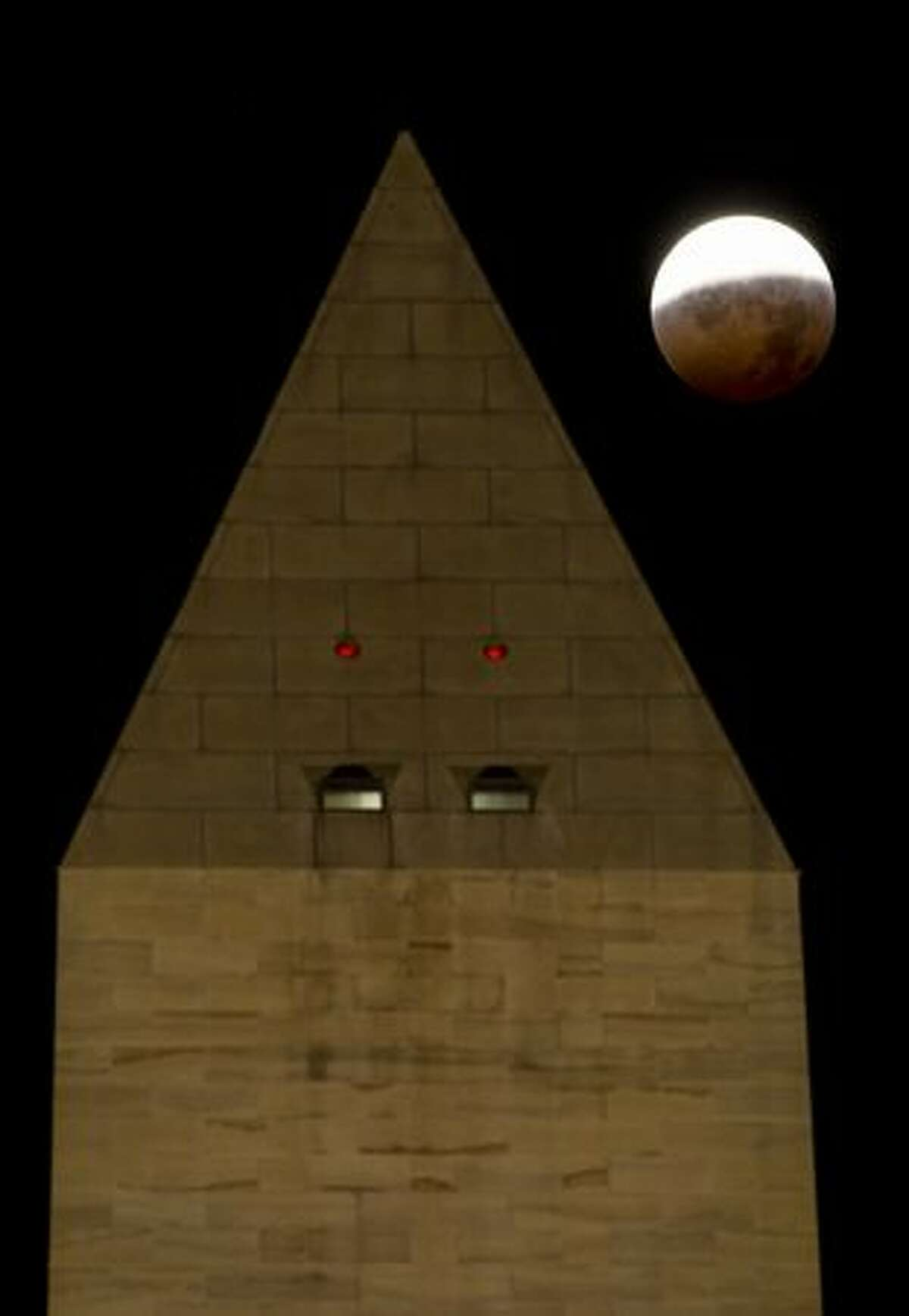 WIn this handout photo provided by NASA, A total lunar eclipse is seen behind the Washington Monument as the full moon is shadowed by the Earth on the arrival of the winter solstice, on Tuesday in Washington, DC. It is the first lunar eclipse that has coincided with the Winter Solstice, the shortest day of the year, since 1638.