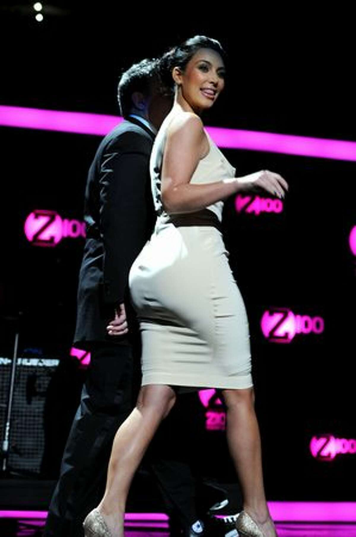 Host Elvis Duran of Z100 and Kim Kardashian walk onstage.