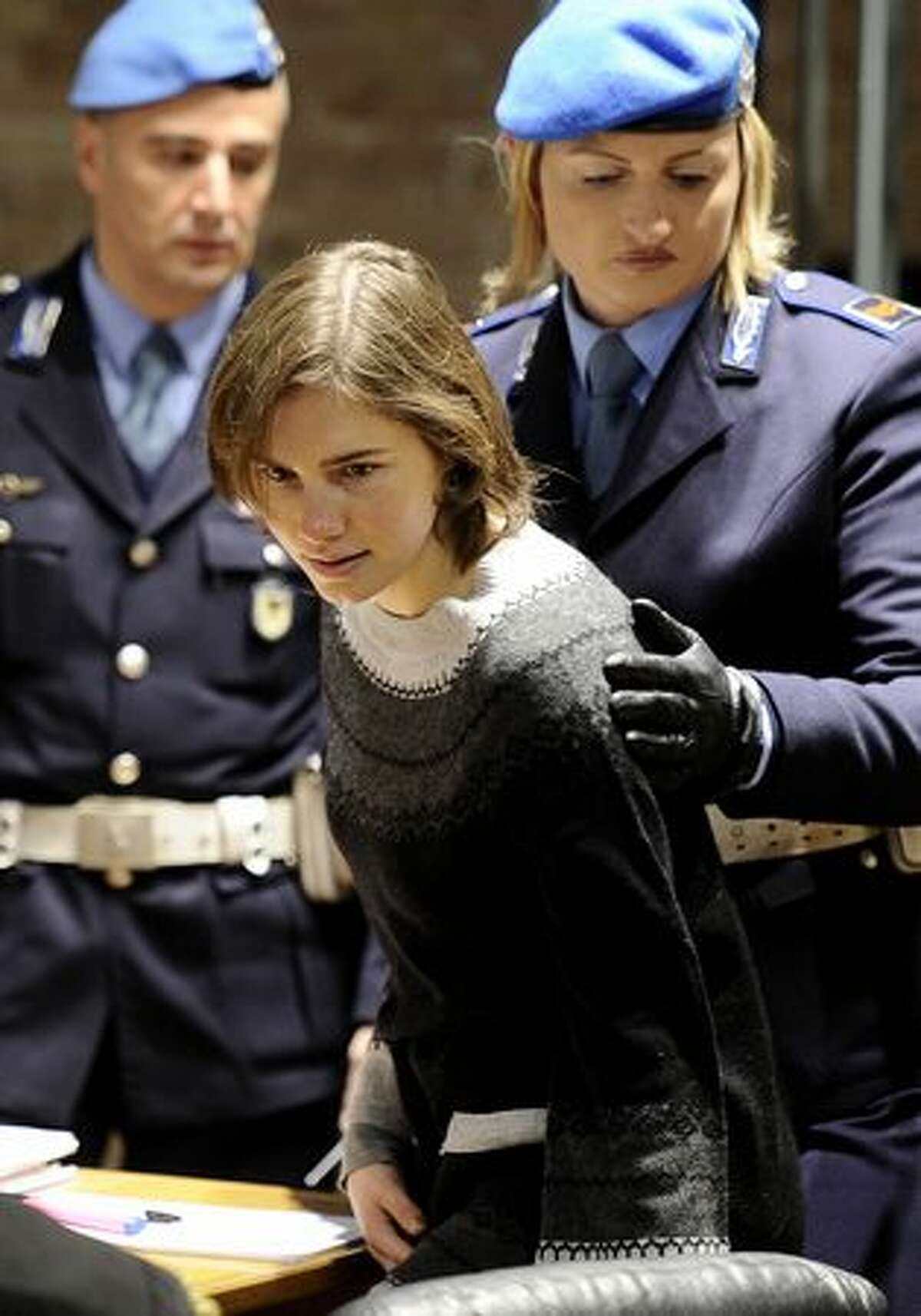 Amanda Knox (center) arrives in court before the start of the second hearing of her appeal. Lawyers for Knox said they would question DNA evidence linking her to the crime.