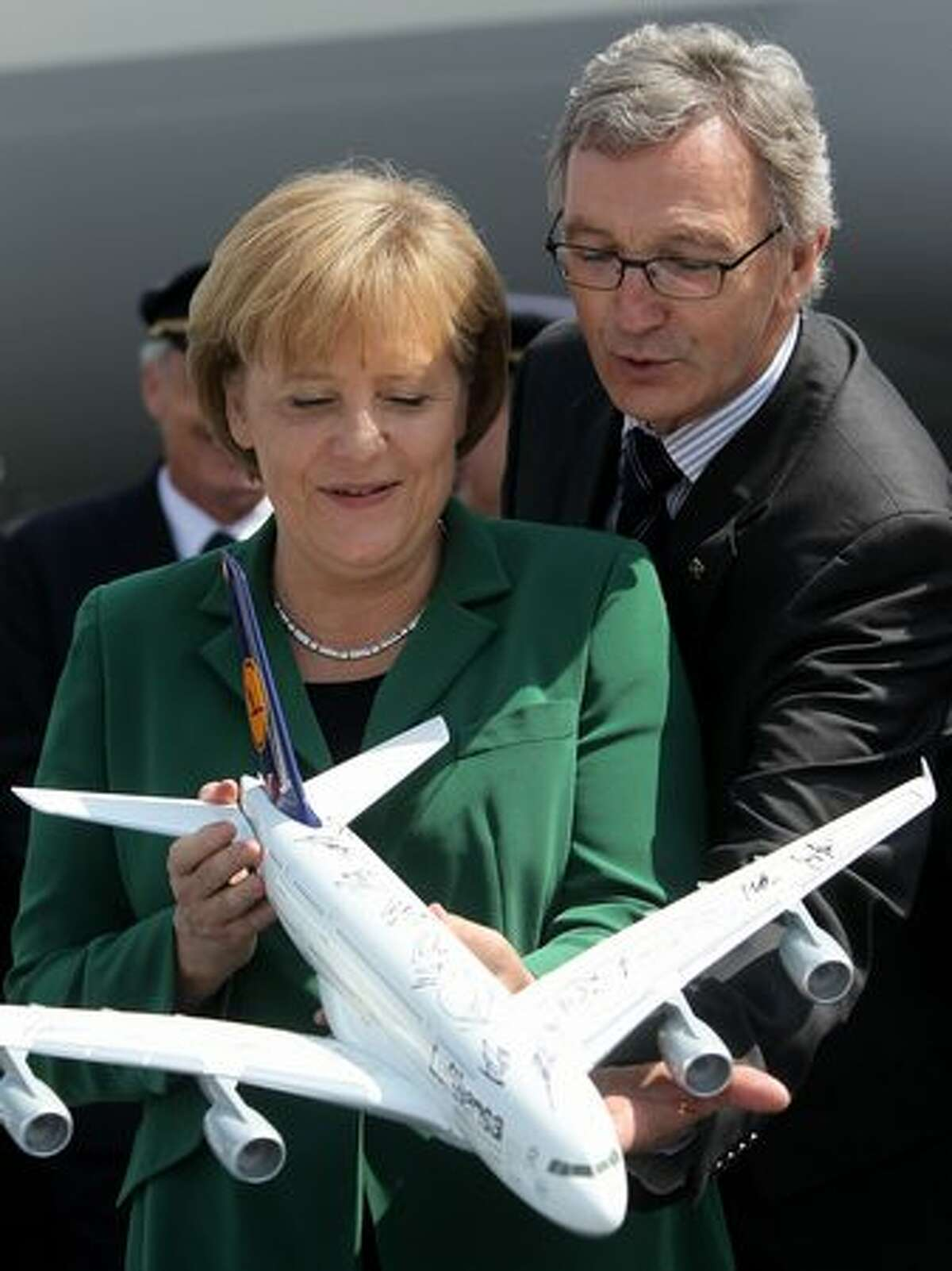 German Chancellor Angela Merkel poses with Lufthansa Chairman Wolfgang Mayrhuber and a model of an Airbus A380 airliner at the ILA Berlin Air Show.