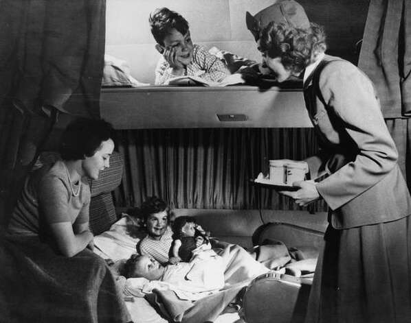 A stewardess serves passengers in a sleeping berth aboard a Boeing 377 Stratocruiser. Photo: Museum Of Flight