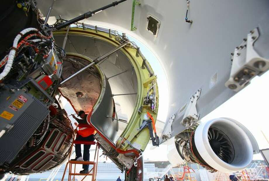 Mike Feeney works on one of the engines on Boeing's new 747-8 at Everett's Paine Field. The 747-8 is the fourth-generation of the aircraft, with a lengthened fuselage, redesigned wings and improved efficiency. Photo: Joshua Trujillo, Seattlepi.com