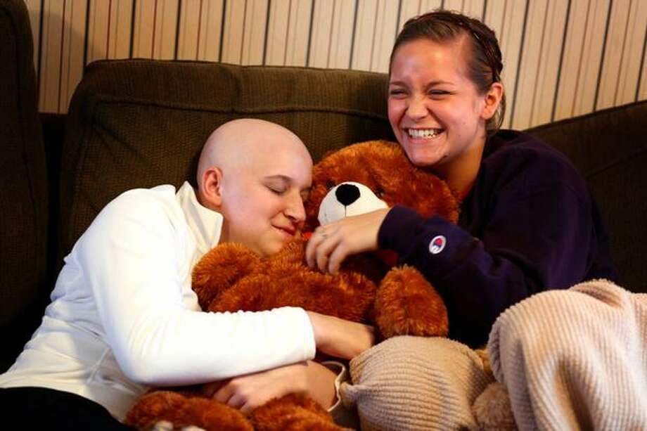 Ashley Aven, left, hugs a bear given to her by former softball teammate Stephani Bernard in Ashley's Lynnwood home. Ashley, 17 years-old and a softball player at Meadowdale High School, put up a valiant fight against acute myeloid leukemia, a rare and aggressive disease. In early January doctors gave her less than 2 months to live. She battled the disease for nearly 8 months. Aven died in August, after touching the hearts of many people with the story of her struggle. Photo: Joshua Trujillo, Seattlepi.com